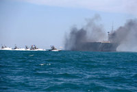 With rockets roaring and guns blazing, more than a dozen swarming Iranian speedboats assaulted a replica of a U.S. aircraft carrier Wednesday during large-scale naval drills near the strategically...