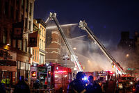 Four apartment buildings in New York's East Village neighborhood caught fire from an apparent gas explosion on Thursday and three collapsed, causing 19 injuries, authorities said.