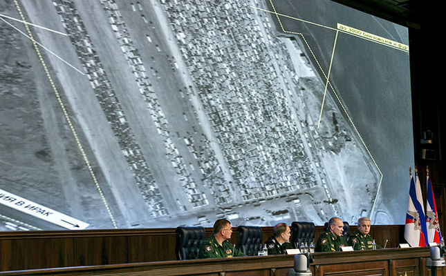 Russian top military officials speak to the media in front of an aerial image which they say is oil trucks near Turkey's border with Syria is displayed by the Russian Defense Ministry at a briefing in Moscow, Dec. 2, 2015. (AP Photo)