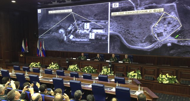 Russian top military officials speak to the media in front of an aerial images they say are oil trucks near Turkey's border with Syria displayed by the Russian Defense Ministry, Dec. 2, 2015. (AP Photo)