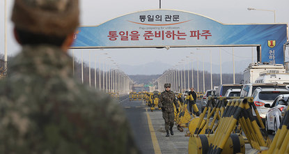 Under the gaze of armed soldiers, large white trucks streamed across the worlds most armed border Thursday as South Korean workers on Thursday began shutting down a jointly run industrial park in...