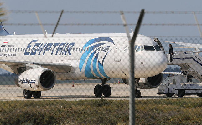 A crew member of the hijacked aircraft of EgyptAir is seen on the passenger steps after landing at Larnaca airport Tuesday, March 29, 2016. (AP Photo)