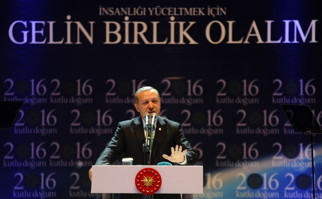 President Erdoğan reacts as he gives a speech in front of a poster with the slogan that reads Lets join hands to dignify the humanity in Istanbul on Sunday.
