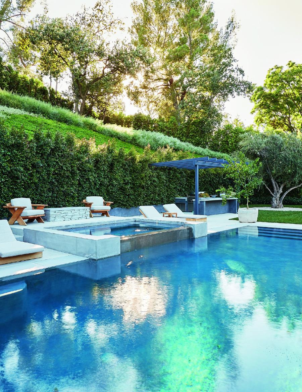 Beyaz minderli koltuk ve şezlonglarla Jenner'ın evinde şık havuzbaşı.