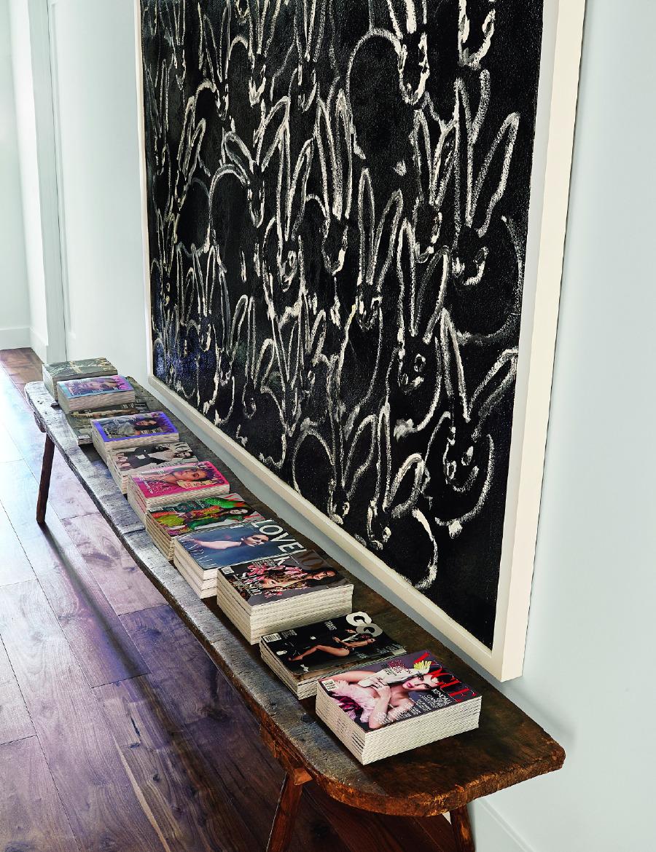 Ofis bölümünde dergilerin durduğu antika ahşap sıra, Hunt Slonem tablo.
