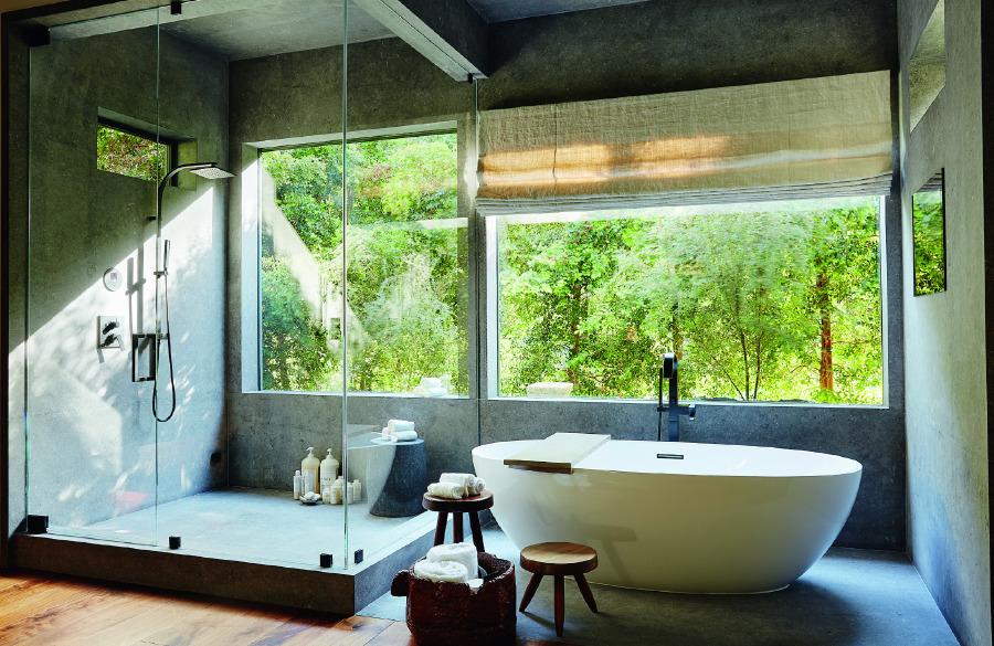 Kireçtaşı kaplama ana banyoda vintage Perriand tabure.